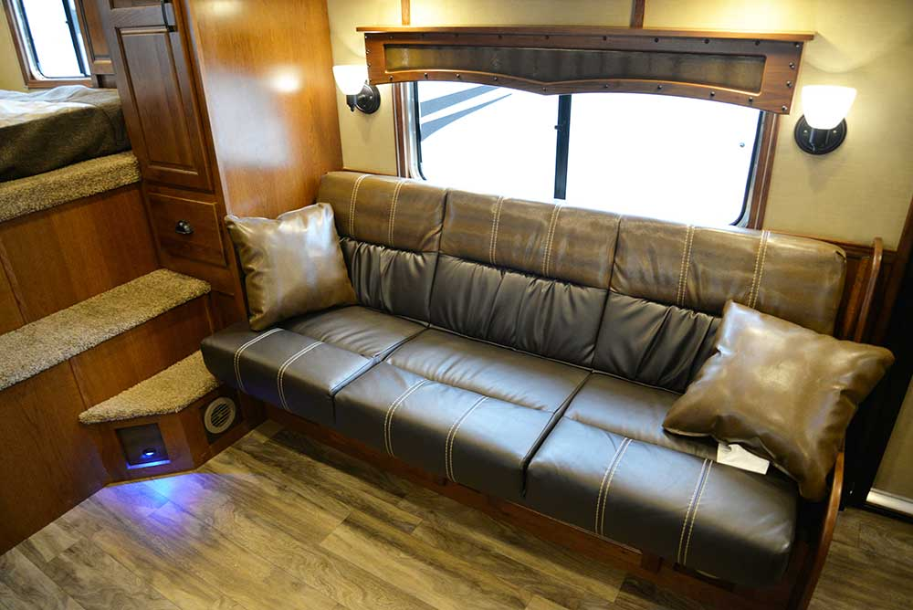 Sofa in living area in a Bighorn BH8X15DSRK | Lakota Trailers