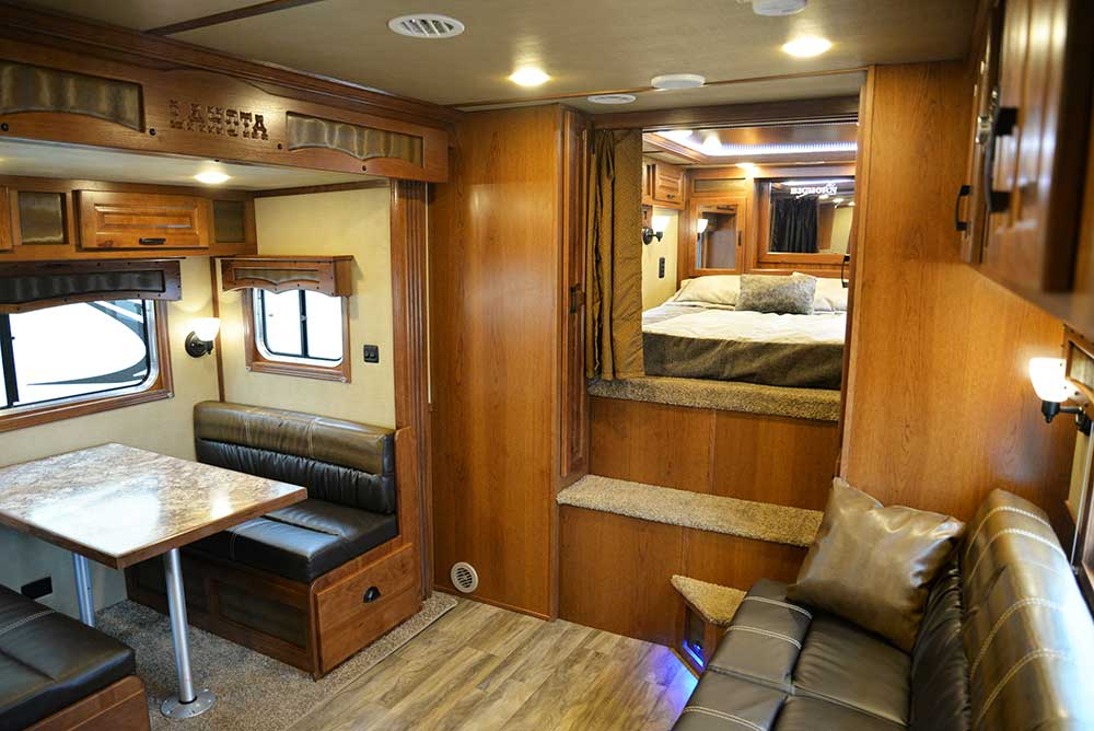 Living area and bedroom in a Bighorn BH8X15DSRK | Lakota Trailers