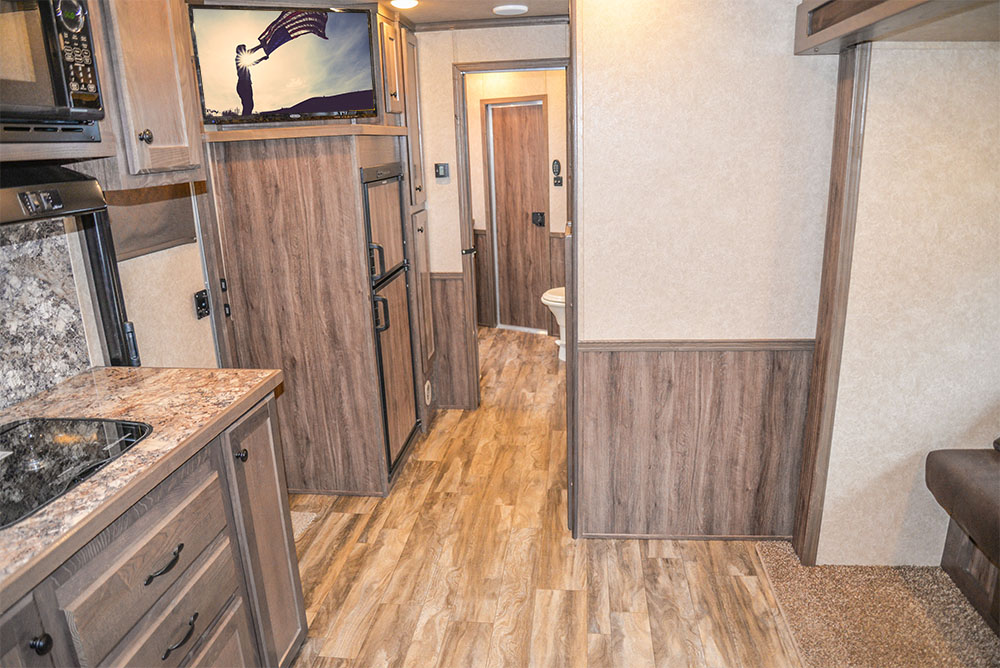 Sofa in the Slide-Out in a LE8X16BB - Charger Livestock Edition Trailer | Lakota Trailers