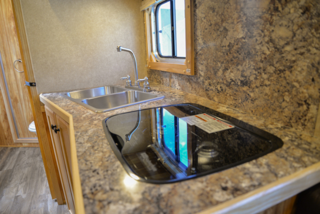 Kitchen sink and stove in Charger C8X11DR | Lakota Trailers